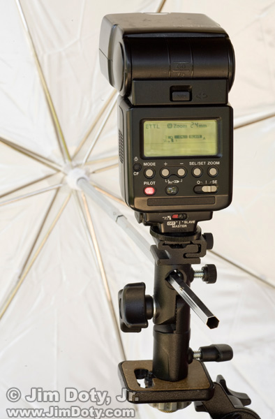 Flash, flash adapter, and umbrella mounted on a tripod.