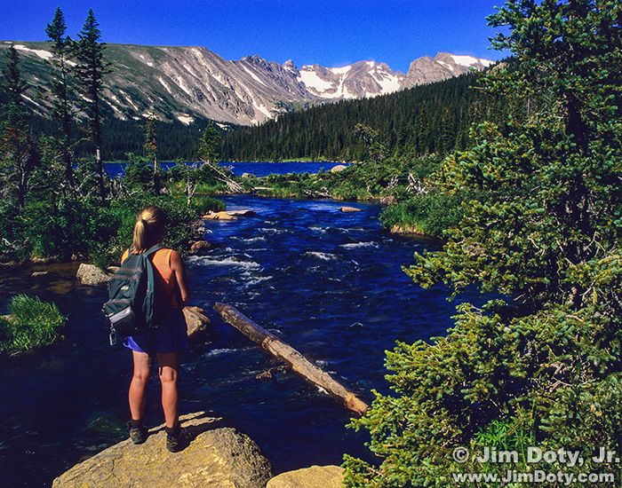 Hiker at the steam flowing out of Long Lake. Indian Peaks Wilderness, Colorado.