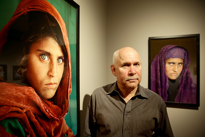 "Photographer Steve McCurry next to his images of Sharbat Gula, ""Afghan Girl""."